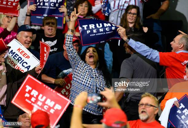 A woman is escorted out of the building as US President Donald Trump speaks on stage during a campaign rally at the Target Center on October 10 2019...