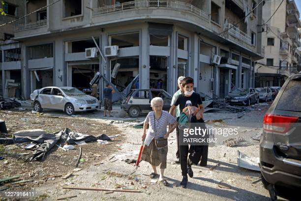 A woman is evacuated from the partially destroyed Beirut neighbourhood of Mar Mikhael on August 5 2020 in the aftermath of a massive explosion in the...