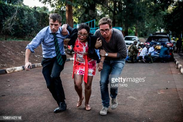 TOPSHOT A woman is evacuated from the scene of an explosion at a hotel complex in Nairobi's Westlands suburb on January 15 in Kenya A huge blast...
