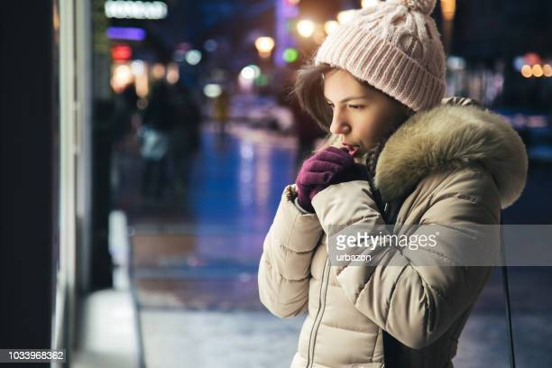 woman is feeling cold downtown - shaking stock pictures, royalty-free photos & images
