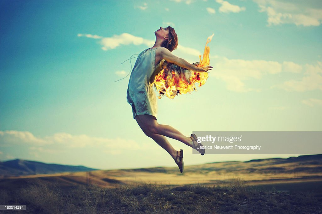Woman is fiery wings rising against a turquois sky : Stock Photo