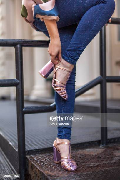 woman is fixing her shoe in the street - human leg stock photos and pictures