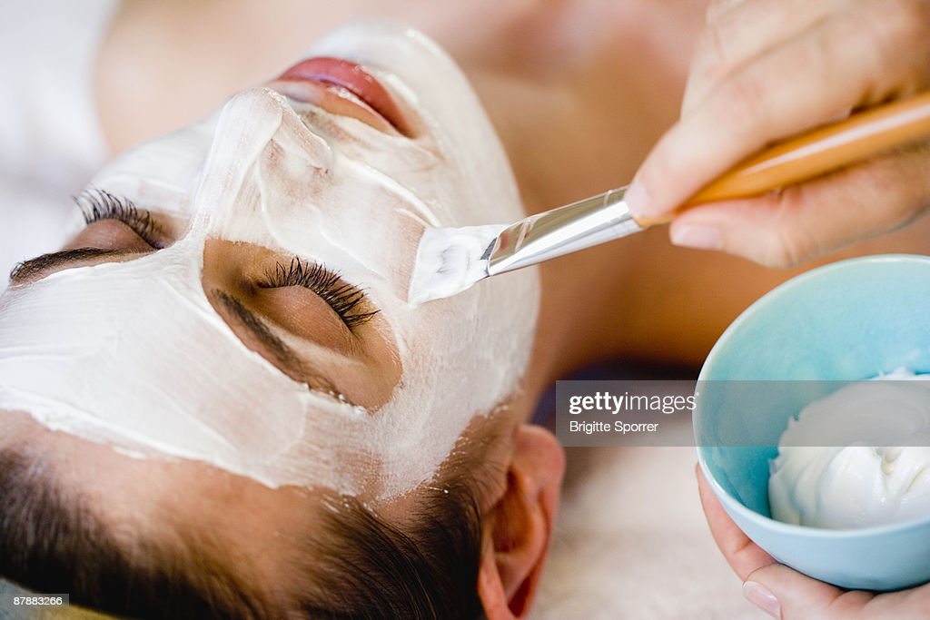 Woman is getting a face mask : Stock Photo
