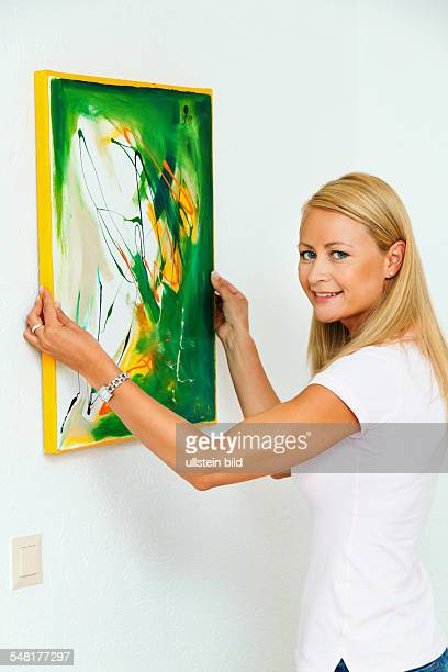 woman is hanging up a picture