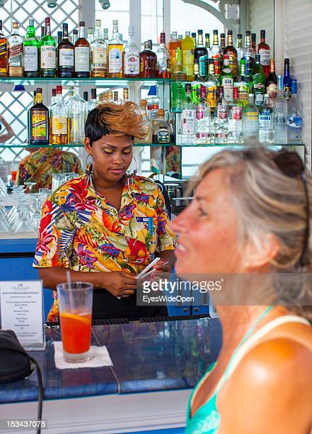 Woman is having a drink at the bar of luxury Resort and Hotel Cape Santa Maria which is having one of the Bahamas´ best beaches with white sand and...