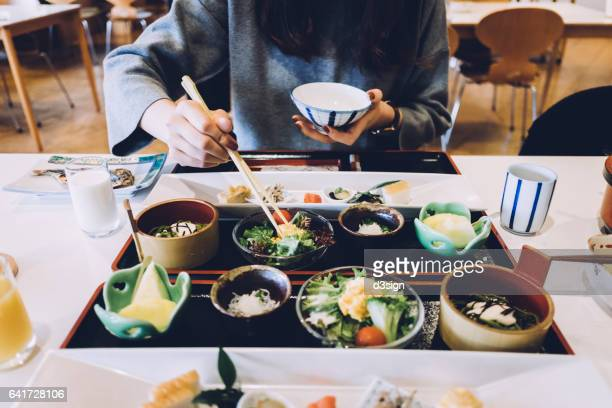 Woman is having meal in a Japanese restaurant