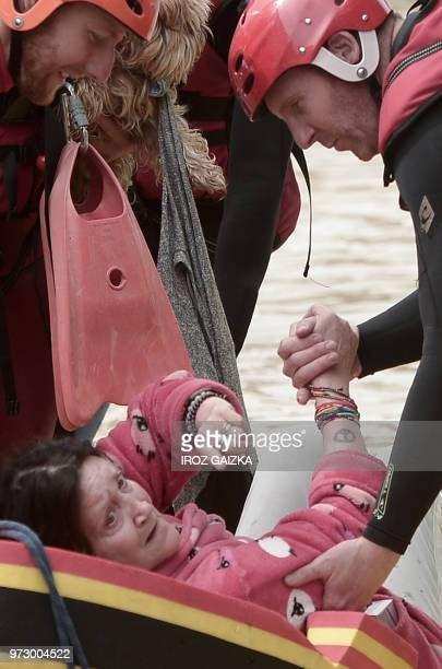 A woman is helped by firemen into a small dinghy following heavy rains in SaliesdeBearn south western France on June 13 2018