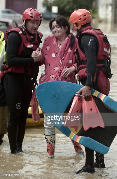 A woman is helped by firemen through flood waters following heavy rains in SaliesdeBearn south western France on June 13 2018