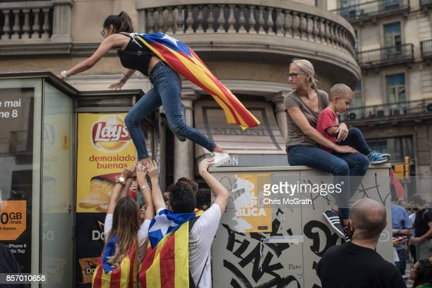 A woman is helped by friends to climb onto a bus stop as thousands of citizens gather in Plaza Universitat during a regional general strike to...