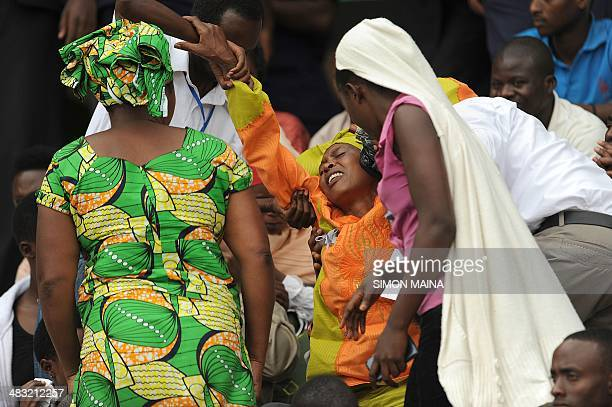 A woman is helped out of the the Amahoro stadium in Kigali on April 7 during a ceremony marking the 20th anniversary of Rwanda's genocide Rwandan...