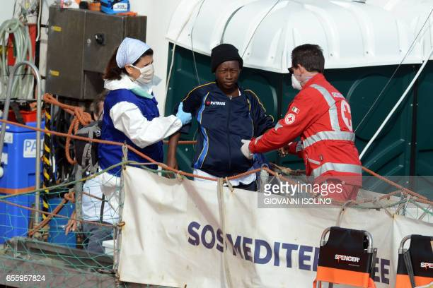 A woman is helped to disembark in the port of Catania on the island of Sicily on March 21 2017 from the ship 'Aquarius' following a rescue operation...