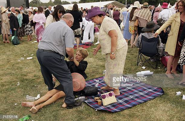 Woman is helped to her feet as race-goers make their way home after Ladies' Day, the third day of Royal Ascot, at the Ascot Racecourse on June 22,...