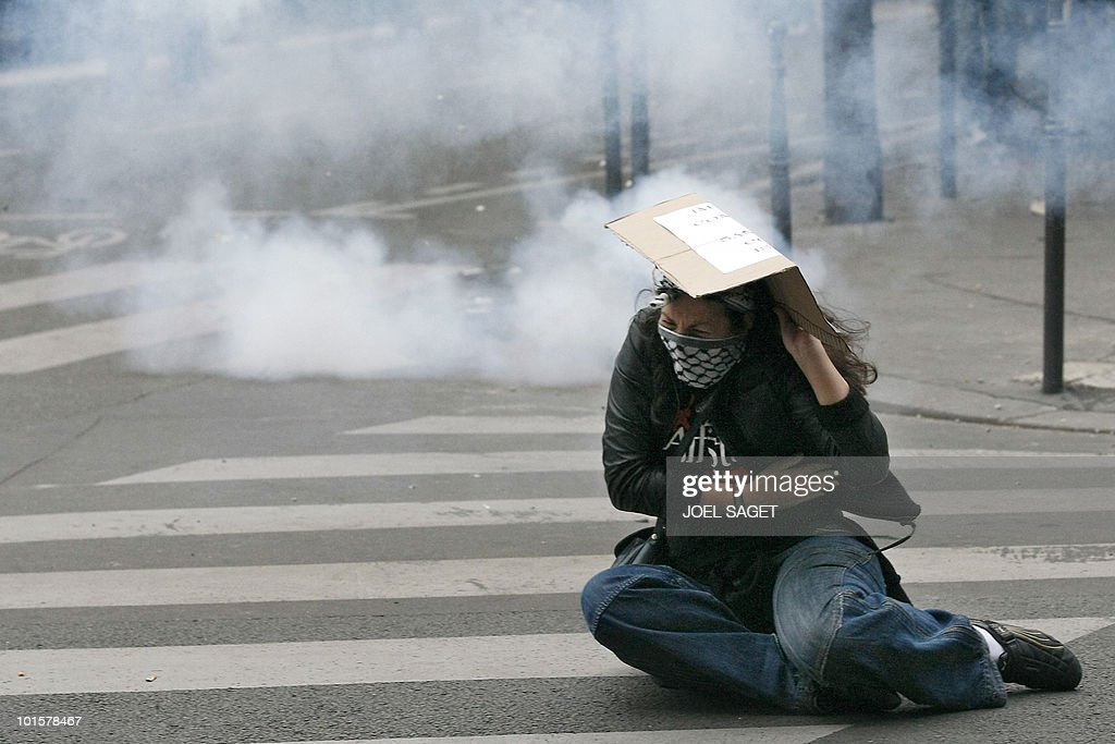 A woman is hit by a fragment of a tear gas shot by French anti-riot policemen near the Israeli embassy in Paris on May 31, 2010 during a demonstration against Israel's deadly raid on an aid flotilla bound for Gaza Strip. France's President Nicolas Sarkozy accused Israel of a 'disproportionate use of force' after Israeli naval forces stormed six ships bound for besieged Gaza with thousands of tonnes of aid and hundreds of pro-Palestinian activists aboard.