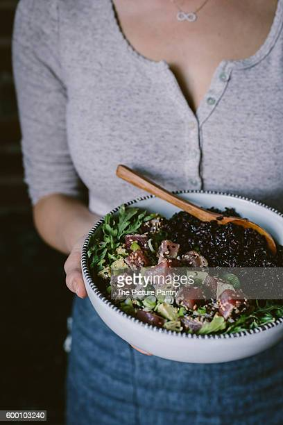 A woman is holding a bowl filled with Sesame Crusted Seared Tuna Salad and forbidden rice.