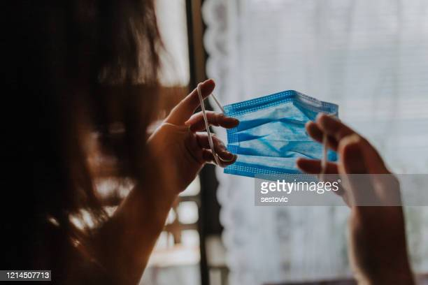 woman is holding a covid-19 anti-coronavirus mask as protection against infection - coronavirus mask stock pictures, royalty-free photos & images
