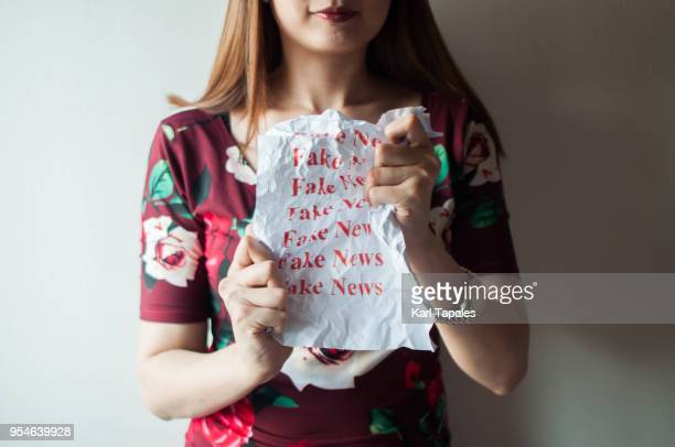 A woman is holding a piece of paper with fake news