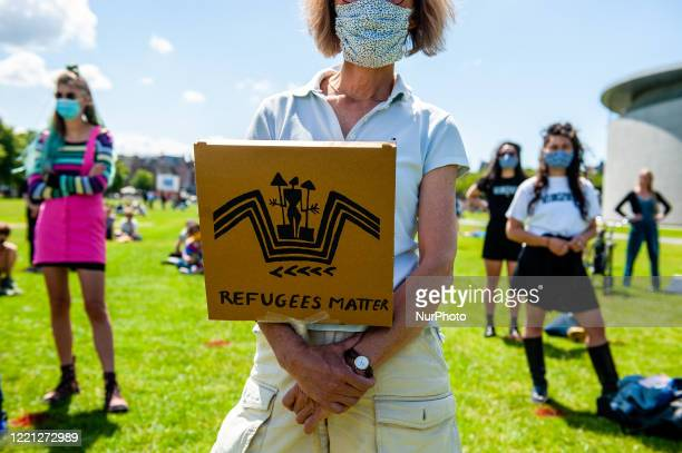 Woman is holding a placard in support of the refugees while wearing a mouth mask, during the Refugee Lives Matter demonstration in Amsterdam,...