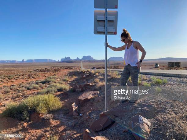 a woman is holding a street sign at the popular overlook of monument valley - fitopardo stock pictures, royalty-free photos & images