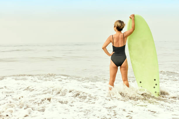 A woman is holding a surfboard at the beach.
