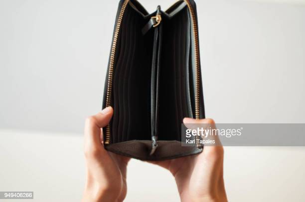 a woman is holding an empty wallet - clutch bag stock photos and pictures