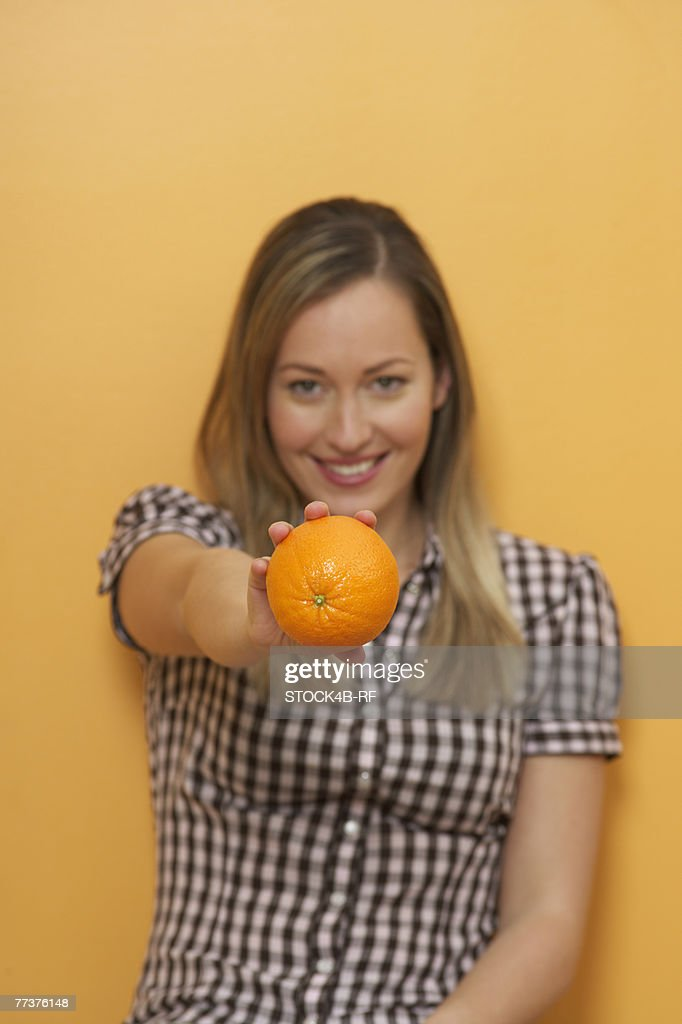 A woman is holding an orange in her hand : Photo