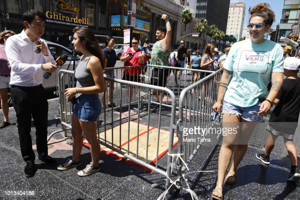 A woman is interviewed at a barricade surrounding the location of the vandalized Hollywood star of President Donald Trump along the Hollywood Walk of...