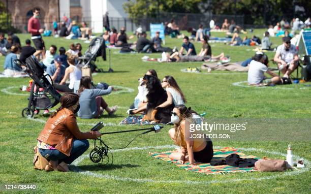 A woman is interviewed from inside a painted circle on the grass encouraging social distancing at Dolores Park in San Francisco California on May 22...