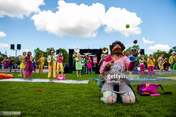 Woman is juggling with balls during the Refugee Lives Matter demonstration in Amsterdam, Netherlands on June 20th, 2020.