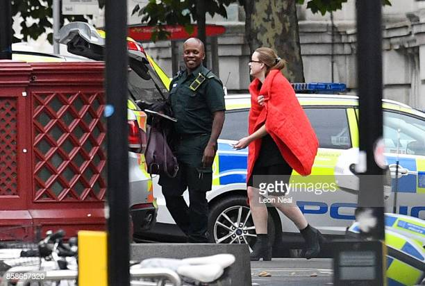 A woman is led through a police cordon after a car mounted the pavement and collided with pedestrians outside the Natural History Museum on October 7...