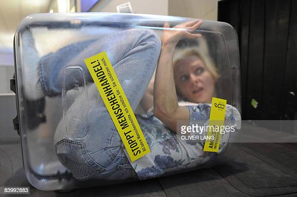 A woman is locked up in a transparent suitcase reading Stop Human Trafficking 60 Years of Human Rights on a luggage belt at the airport in Munich...