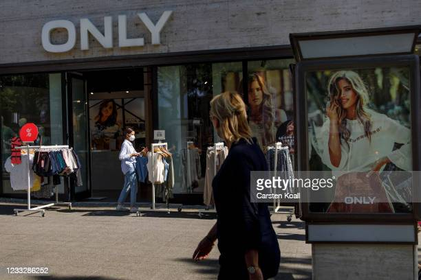 Woman is looking among clothes in a store on the second day that people are no longer required to show a negative Covid test result to enter...
