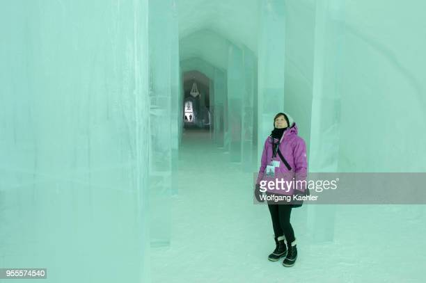 A woman is looking at the interior of the classic Icehotel in Jukkasjarvi near Kiruna in Swedish Lapland northern Sweden
