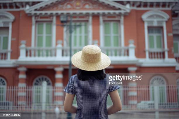 a woman is looking at the vintage house. - 若い女性一人 ストックフォトと画像