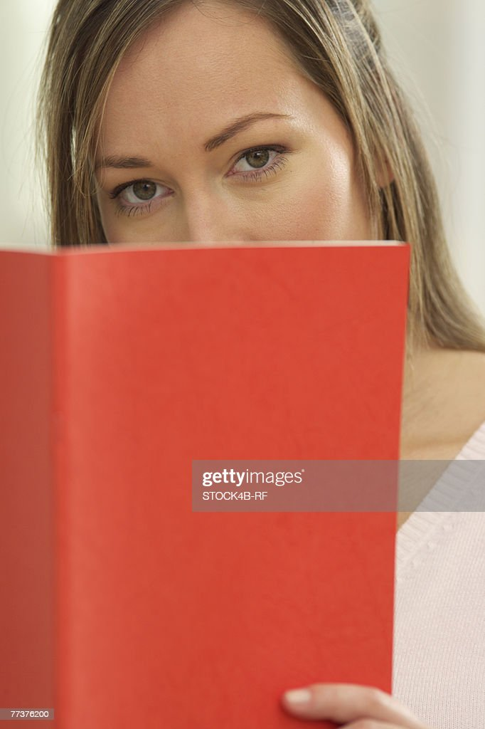 A woman is looking behind a book : Photo