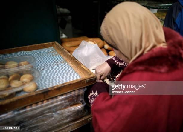 A woman is looking for small change at a bakery street scene in the Muslim quarter in the historic city center of Jerusalem on February 08 2017 in...