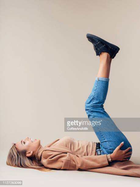 woman is lying down on the floor - skinny jeans stock pictures, royalty-free photos & images