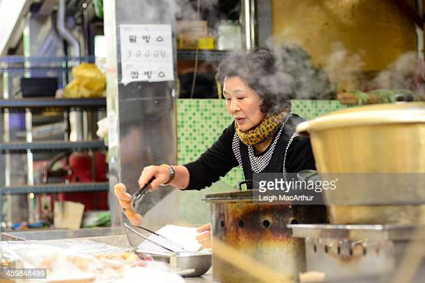 Woman is making and serving homemade doughnuts at her shop in a downtown street market in small town South Korea. Taken in the afternoon, on Sunday,...