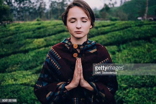 Woman is meditating near the tea plantation