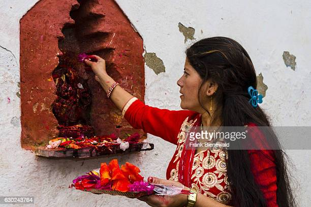 A woman is offering prasad to the statues of gods outside the temple Khadga Devi Mandir at the hinduist festival Darsain