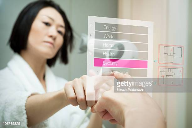 Woman is operating the security system on touchscr