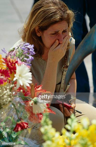A woman is overcome with grief at a memorial arranged at the site of the deadly Santa Monica Farmer's Market crash that killed 10 people and injured...