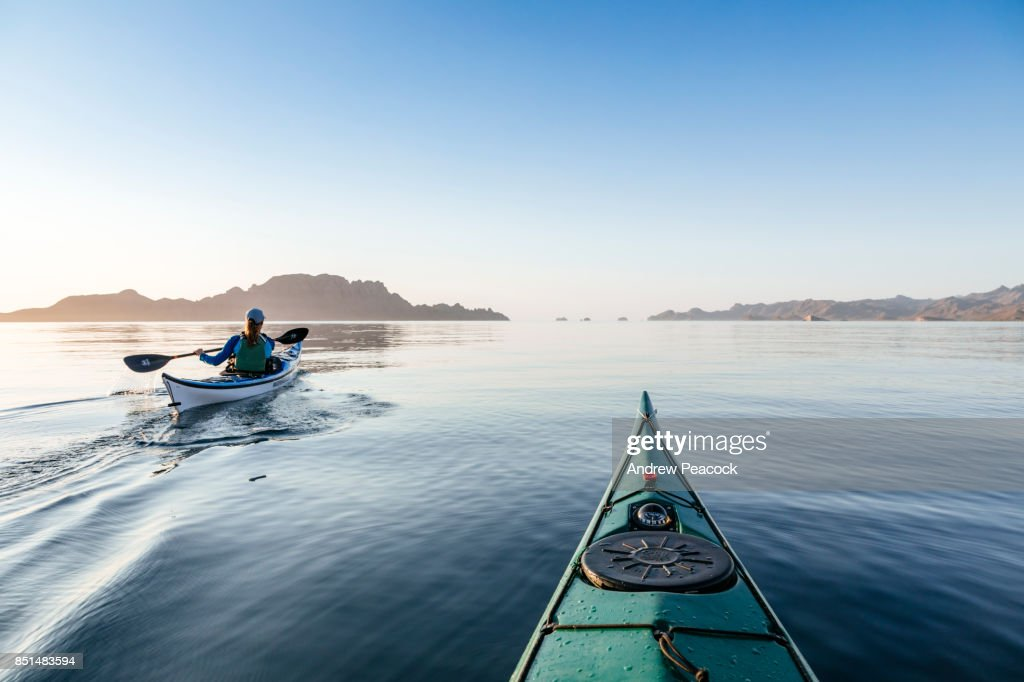 a woman is paddling a sea kayak in calm ocean stock photo getty images