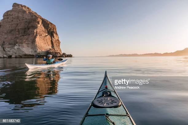 A woman is paddling a sea kayak in calm ocean.