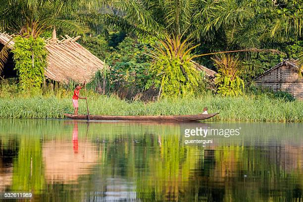 woman is paddling in a pirogue on congo river - democratic republic of the congo stock photos and pictures