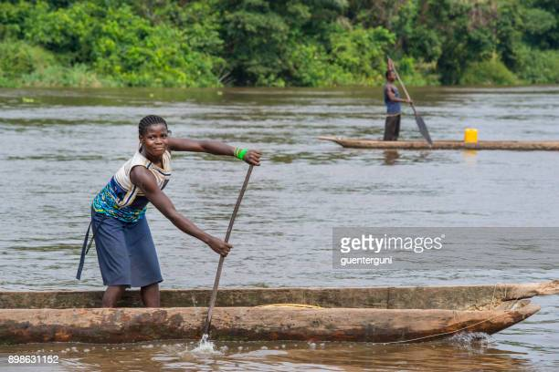woman is paddling in a pirogue on congo river - dugout canoe stock photos and pictures