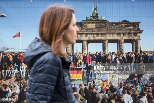 A woman is passing by a poster with a seen from ttthe fall of the Berlin Wall at the entrance to an amusement area set up along 17th of June Street...