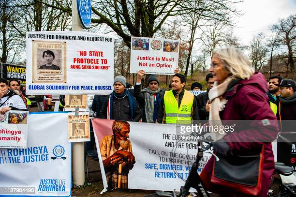 Woman is passing by with her bike in front of a group of people in support of Rohingya, during a Rohingya solidarity rally in front of the ICJ, The...
