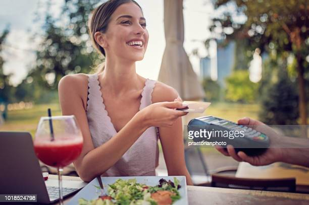 woman is paying using contactless credit card in the bar - paying stock pictures, royalty-free photos & images