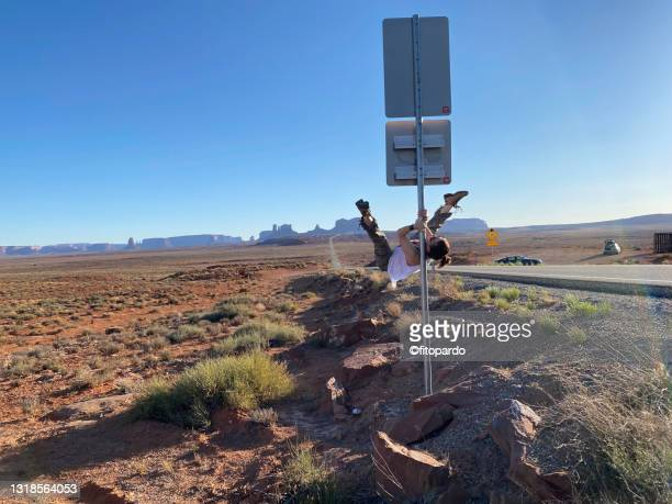 a woman is performing pole fitness on a street sign in front of monument valley in utah - fitopardo stock pictures, royalty-free photos & images