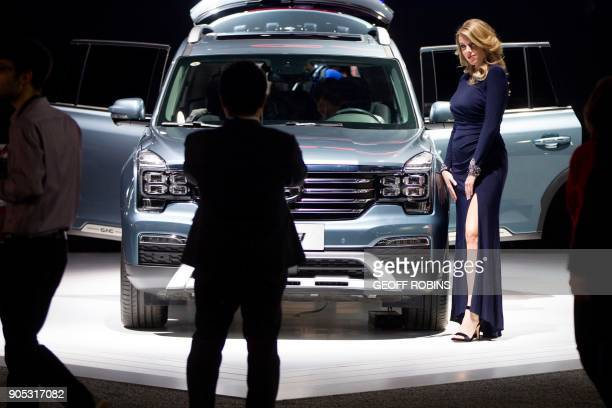 A woman is photographed as she stands next to a car at the GAC booth at the 2018 North American International Auto Show in Detroit Michigan January...